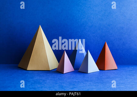 Platonic solid geometric figures. Three-dimensional pyramid rectangular objects on blue background. Yellow blue pink violet red colored tetrahedron abstract shapes objects. - Stock Photo