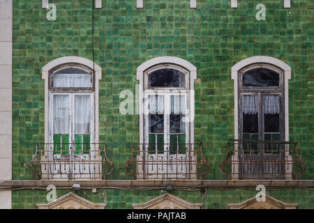 Green traditional portuguese tiles (azulejos) used for the facade of the house. Three large windows with an arch and curtains. Small balconies. Lagos, - Stock Photo