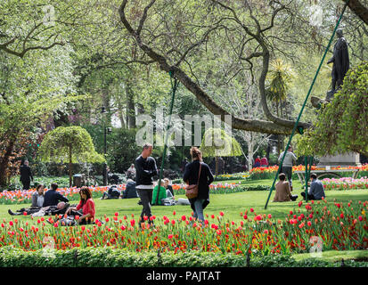 people enjoying a spring day in a public London park - Stock Photo