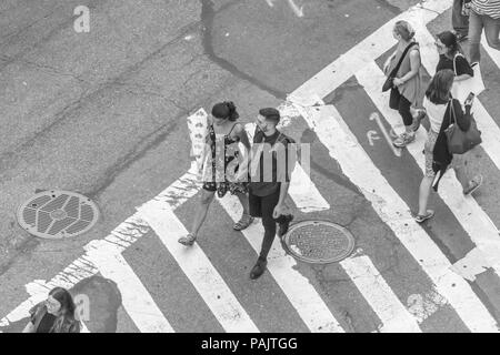 a view from above of people walking in a crosswalk at 61st street and Broadway in New York City - Stock Photo