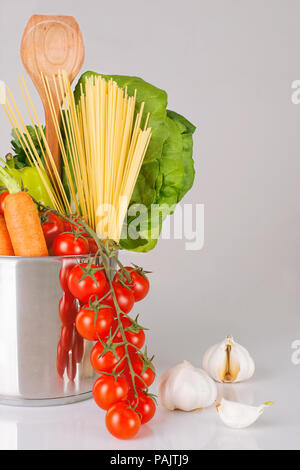 variety of fresh vegetables, scoop and spaghetti in a metal pot on a grey background, vertical, gray backround - Stock Photo