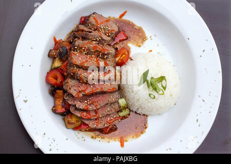 Kobe beef ribeye steak, vibrant, sliced steak on grilled vegetables with rice - Stock Photo