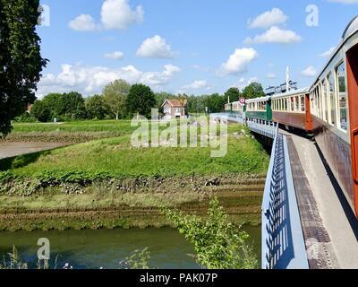 Le Chemin de Fer, Baie de Somme, train with steam locomotive, crossing over a bridge as it departs Saint-Valery-sur-Somme, France. - Stock Photo