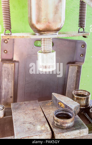 Hydraulic press in a workshop with a hammer head and other stainless steel hard pieces in warm sunlight with soft filter effects applied - Stock Photo