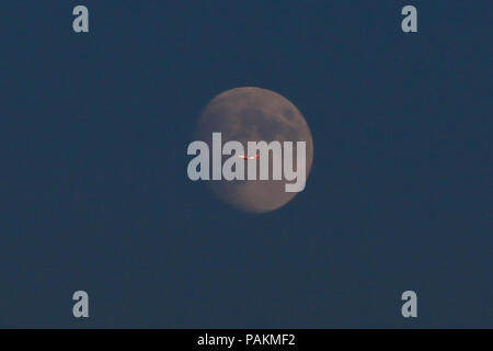 London. UK 24 July 2018 - A plane flies through a nearly full moon over north London. Total lunar eclipse will be visible in London on 27 and 28 July 2018.  Credit: Dinendra Haria/Alamy Live News - Stock Photo
