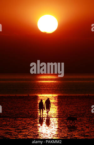 Heacham, Norfolk, UK. 23rd July, 2018. After a very hot day, people walk along the beach at low tide just before sunset in Heacham, near Hunstanton,  Norfolk, on July 23, 2018. © Paul Marriott Credit: Paul Marriott/Alamy Live News - Stock Photo