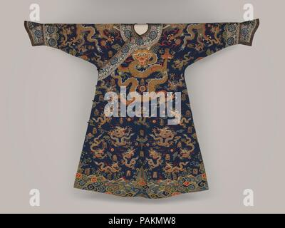 Imperial Court Robe. Culture: China. Dimensions: Overall: 56 x 74 in. (142.2 x 188 cm). Date: 17th century.  On this robe, woven from threads of silk and gold, five-clawed dragons (long), clouds, and flaming jewels appear against a rich blue ground above waves and mountains. Scattered among the dragons are variants of the Chinese character shou (longevity), making this robe an especially appropriate garment for birthday celebrations.   The embroidered neck and sleeve bands were made later than the tapestry-woven textile used for the robe. Museum: Metropolitan Museum of Art, New York, USA. - Stock Photo