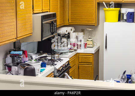 Messy old kitchen with oak cabinets, tile countertops, gas stove, green flooring and piles of dishes. - Stock Photo