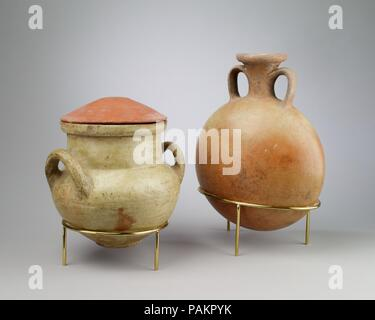 Lentoid Bottle (Pilgrim Flask). Dimensions: H. 27 × Diam. 20 cm (10 5/8 × 7 7/8 in.). Dynasty: Dynasty 18. Reign: reign of Akhenaten. Date: ca. 1353-1336 B.C..  These are marl-clay pots excavated in the North Suburb at Amarna. The lentoid flask (29.7.1) is a type  that originates outside Amarna itself. It probably came with particular trade contents: many such lentoid flasks from Amarna show a pitting on the interior that suggests their special contents was somewhat corrosive. The two-handled jar (29.7.2) is lidded with a small upside down silt-clay dish. It had a brown contents when excavated - Stock Photo