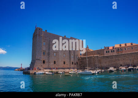 Scenic view of fort of St. Lawrence, the historical harbor and a small pier with a hill house area viewed from top of the old town wall, Dubrovnik. - Stock Photo