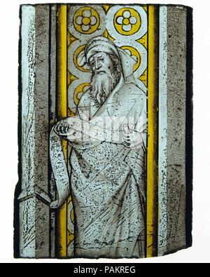 Prophet from a Throne of Solomon. Culture: French or South Netherlandish. Dimensions: Overall: 9 x 4 1/2 in. (22.9 x 11.4 cm). Date: ca. 1390-1410.  Uncommonly refined and gemlike in its painterly finesse, this stained-glass fragment with a prophet is related stylistically to the work of André Beauneveu (1335-1401/3), a gifted sculptor, painter, and illuminator from the South Lowlands, who was employed by King Charles V of France; Louis de Mâle, comte de Flandres; Philippe le Hardi, duc de Bourgogne; and Jean, duc de Berry, among others. A close parallel to the figure style--particularly to th - Stock Photo