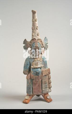 Costumed Figure. Culture: Maya. Dimensions: H. 11 1/2 x  W. 3 13/16 x  D. 3 3/4 in. (29.3 x 9.7 x 9.5 cm). Date: 7th-8th century.  This ceramic figurine depicts a standing male wearing a long textured bodysuit and conical headdress. His mouth is open, as if speaking, and he wears an ornament between his eyes. Incised lines on his cheeks may represent wrinkles, indicating he is a mature individual. He wears a belt and loincloth above the bodysuit, as well as a ruffled collar and large round earflares, or ornaments worn in the earlobes (see 1994.35.591a, b for an example of an earflare set, and  - Stock Photo