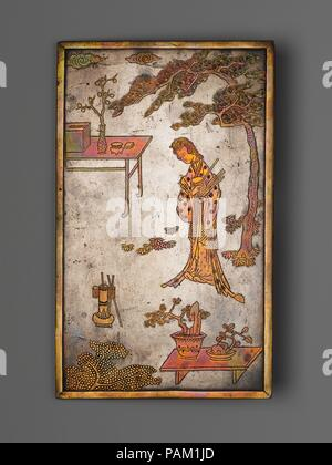Table Screen with Woman Playing Touhu. Culture: China. Dimensions: Screen: H. 8 13/16 in. (22.4 cm); W.. 5 5/16 in. (13.5 cm); D. 3/16 in. (0.5 cm)  Screen with stand: H. 11 3/4 in. (29.8 cm); W. 5 7/8 in. (14.9 cm); D. 4 3/4 in. (12.1 cm). Date: late 17th century.  The woman is playing a game in which arrows are shot into a vase with a narrow neck. On the back of the screen a quote from a Tang dynasty (618-907) poet reads:  To the Master, joyous and deeply grateful is  She to serve and to follow, as though two  Suns are illuminating her saints and ancestors. Museum: Metropolitan Museum of Art - Stock Photo