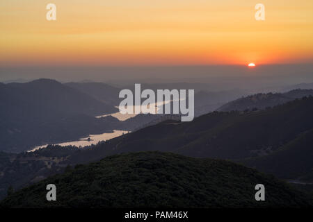 Don Pedro Lake and golden setting sun in the Sierra Foothills, on the  drive to Yosemite National Park - Stock Photo