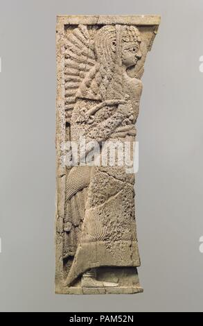 Furniture plaque carved in relief with standing woman. Culture: Assyrian. Dimensions: 9.96 x 3.74 in. (25.3 x 9.5 cm). Date: ca. 9th-8th century B.C..  This ivory panel was found in a storage room in Fort Shalmaneser, a royal building at Nimrud that was used to store booty and tribute collected by the Assyrians while on military campaign. Like many other panels from the same storage room, it was part of a chair or couch back or the headboard of a bed. Twenty pieces of furniture were discovered stacked in orderly rows in this room, where they had been stored before the destruction of the Assyri - Stock Photo