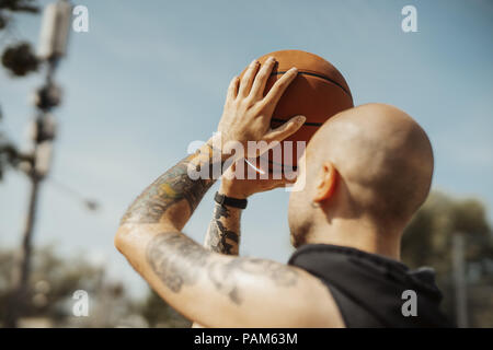 Close up of bald attractive man playing basketball on the basketball court. - Stock Photo