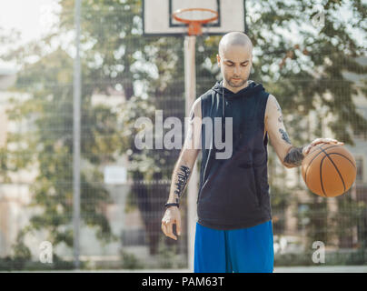 Bald attractive man playing basketball on the basketball court. Man is on focus and foreground, background is blurred. - Stock Photo