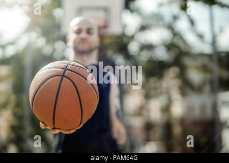 Close up of bald attractive man holding basket ball. Ball is on focus and foreground. Man, basketball hoop and board are on background and blurred. - Stock Photo