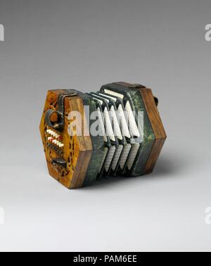 Concertina. Culture: British. Dimensions: W. across ends 15.9 cm (6 1/4 in.)  point to point: 18.3 cm (7 1/4 in.)  D. (closed) 10.8 cm (4 in.). Maker: Charles Wheatstone (1802-1875). Date: ca. 1862.  A student model with colored buttons to facilitate the orientation of the fingers: the white buttons are for diatonic tones, red is C, the black buttons are the accidentals. Museum: Metropolitan Museum of Art, New York, USA. - Stock Photo