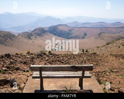 Empty wooden bench overlooking mountains and arid landscape of Malolotja Nature Reserve, Swaziland, Southern Africa. Malolotja Nature Reserve is one o - Stock Photo