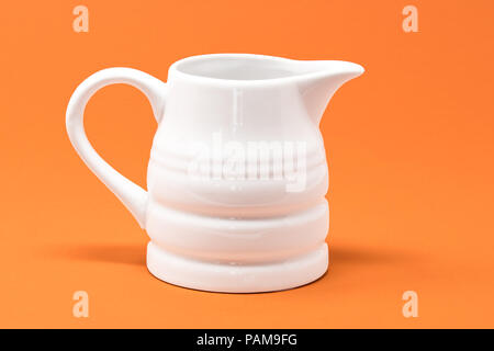 A white jug set against a bright orange background - Stock Photo