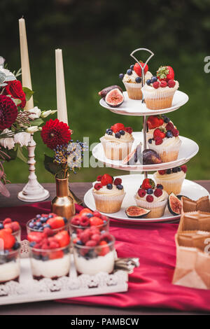 Fresh tasty cupcakes with berries on wedding reception table, decorated in red colour with flowers - Stock Photo