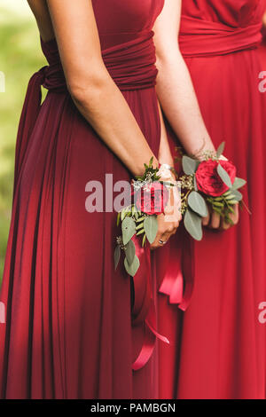Flower bracelets with red roses and silk ribbons. Bridesmaids in red dresses, american style wedding - Stock Photo
