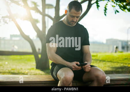 Close up of young man sitting at bench and typing text message on mobile phone outdoors in the park. Front view. - Stock Photo