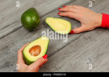Top view - woman hand with red nails, holding avocado cut in half, with other whole green pear in back, on gray wood table - Stock Photo