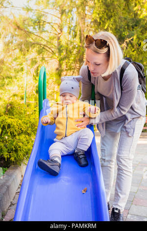 Mom and son ride the slide on the playground - Stock Photo