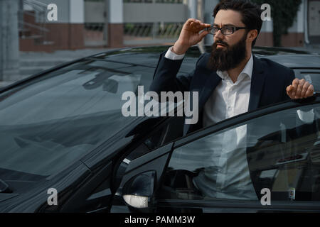 Confident man in formal wear holding hand on opened car door wat - Stock Photo