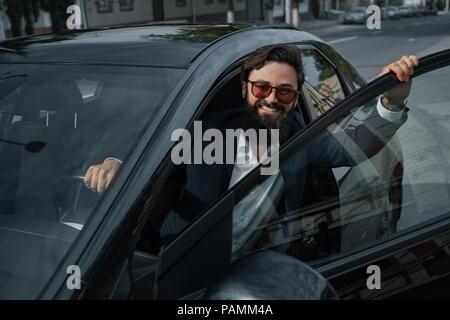 Portrait stylish, handsome man near car outdoors - Stock Photo