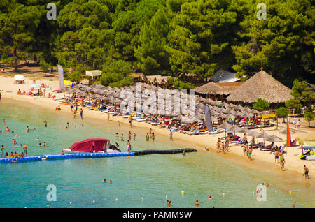 Crowded tropical beach with blue water, golden sand, exotic umbrellas and green trees on the background - Stock Photo