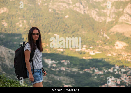 Young backpacking adventurous woman hitchhiking on the road. Traveling backpacks volume, packing essentials. Travel lifestyle. Low budget traveling. - Stock Photo