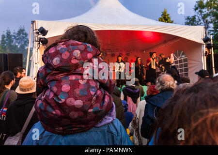 Girl on her dad's shoulders, watching a folk music live show in the park - Stock Photo