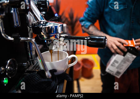 Fancy stainless steel coffee machine pouring a double espresso in a coffee shop - Stock Photo