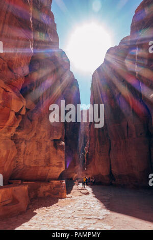 Tourists are dwarfed by the narrow canyon walls on the walk into the Lost City of Petra, Jordan - Stock Photo