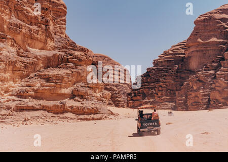 pickup tricks full of tourists drive in a convoy across the red desert sands in the famous Wadi Rum National Park, Jordan - Stock Photo