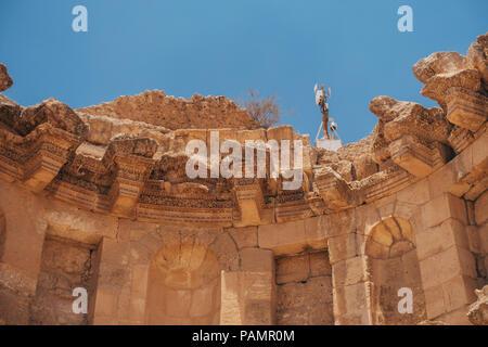 a suriveillance CCTV camera sits atop old ruins in Jerash, Jordan - Stock Photo