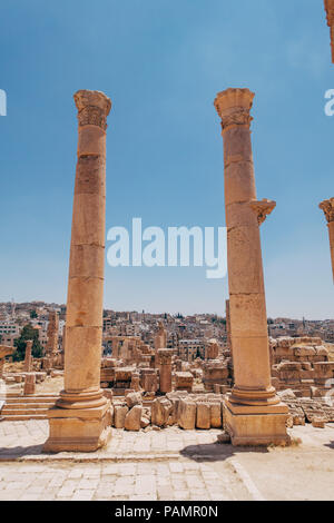 two ancient Greco-Roman columns stand tall at the entrance to an old palace in Jerash, Jordan - Stock Photo