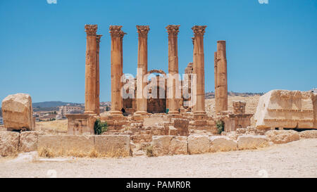 old ancient Greco-Roman columns line cobblestone streets on a warm summers day in Jerash, Jordan - Stock Photo