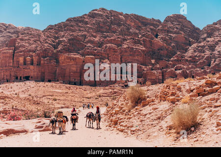 men on mules trek down the main path in front of the tombs in the Lost City of Petra, Jordan - Stock Photo