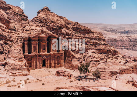 looking down at the Ad-Deir Monastery carved into the side of layers of rock in the Lost City of Petra, Jordan - Stock Photo