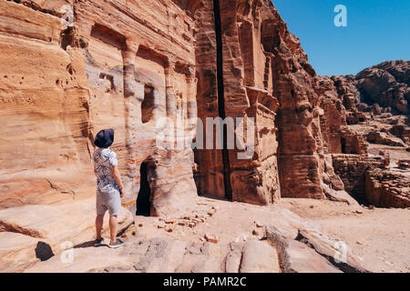 a tourist poses on a rock ledge looking over a tomb entrance in the Lost City of Petra, Jordan - Stock Photo