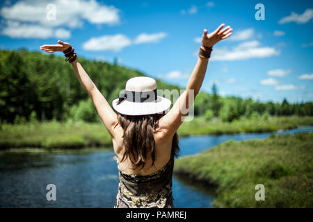 Woman wearing summer hat with her arms up enjoying a beautiful sunny day by the river, seen from behind - Stock Photo