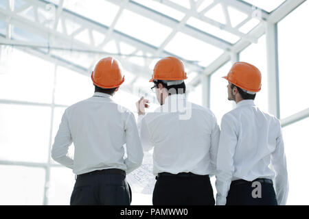 group of business people in safety helmets standing in a new building - Stock Photo