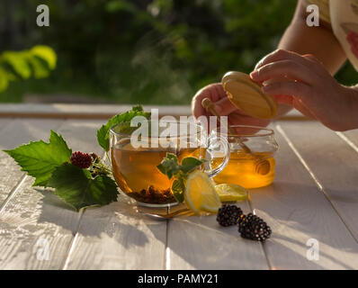 Healthy breakfast concept. Aromatic tea cup, berries and honey on a white wooden table in the garden - Stock Photo