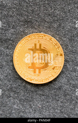 Golden bitcoin on grey background. Bitcoin is a modern way of exchange and this crypto currency is a convenient means of payment in the financial and  - Stock Photo