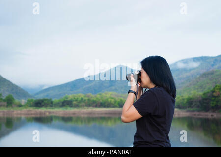 Young traveler woman backpacker use camera take a photo of beautiful of natural lake and mountain view,Freedom wanderlust concept - Stock Photo