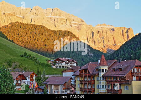 Colorful sunset on Sella Group mountains viewed from Selva with traditional houses in the foreground, Val Gardena, Dolomites, Italy - Stock Photo